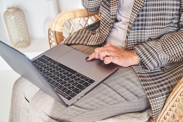 Geschäftsfrau, die an laptop in einem bequemen rattan-korbsessel im schönen innenraum ihres landhauses arbeitet