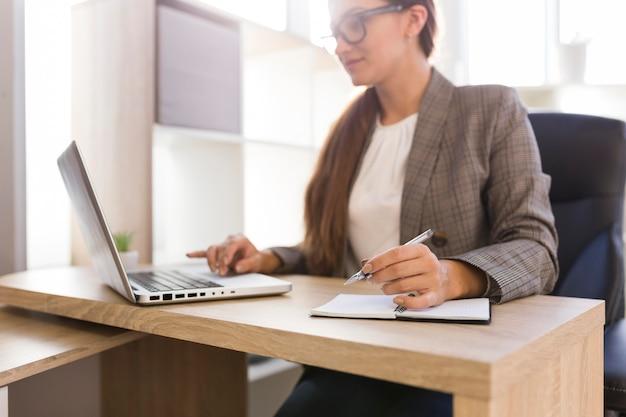 Geschäftsfrau, die an laptop von ihrem büro arbeitet