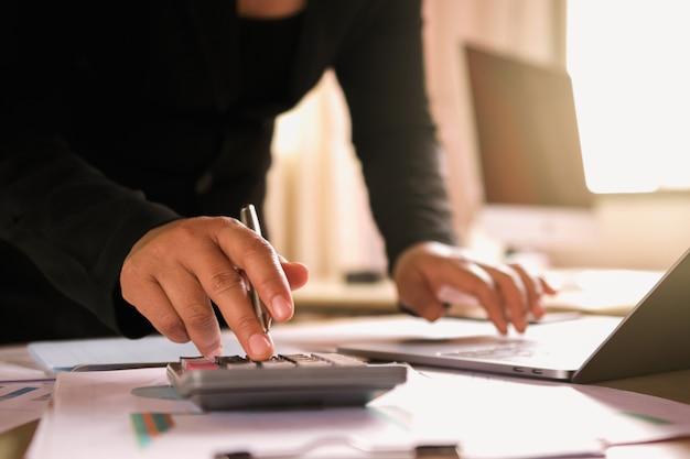 Geschäftsfrau, die an schreibtisch unter verwendung des laptops für kontrolldaten der finanzierung im büro arbeitet