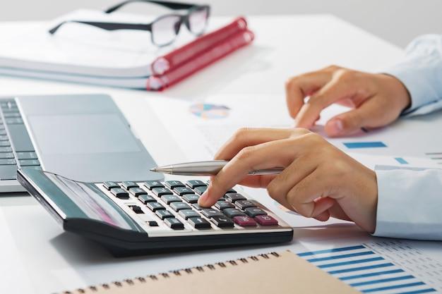 Geschäftsfrau, die an schreibtisch unter verwendung des taschenrechners analysiert finanzbuchhaltung im büro arbeitet