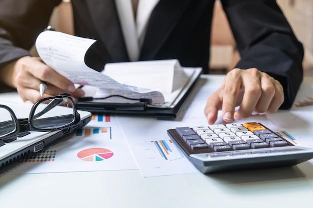 Geschäftsfrau, die an schreibtischbüro mit marketing-diagrammstatistikanalyse arbeitet