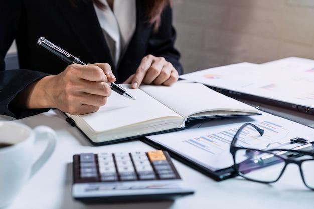 Geschäftsfrau, die an schreibtischbüro mit marketinggraphstatistikanalyse arbeitet