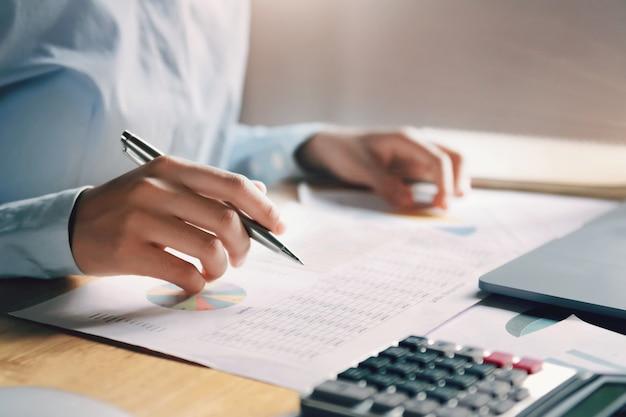 Geschäftsfrau, die an schreibtischkontrolldaten der finanzierung im büro arbeitet