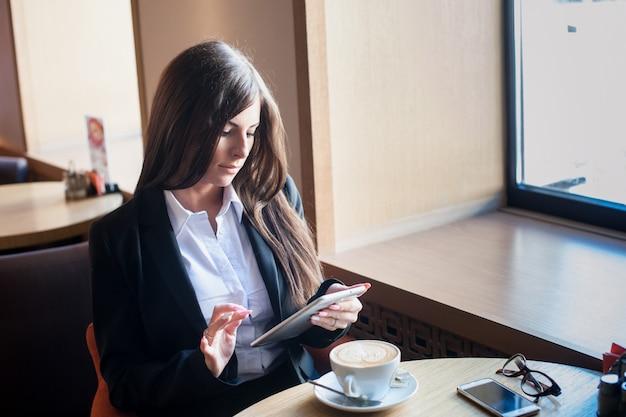 Geschäftsfrau, die an tablet-computer beim trinken des kaffees im büro arbeitet