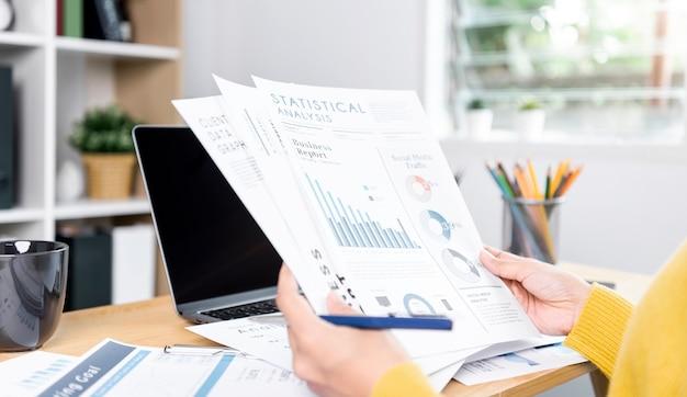 Geschäftsfrau, die analyse-dokument-grafik-finance-strategie-statistik-erfolgskonzept und planung für die zukunft im büroraum überprüft.