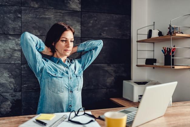 Geschäftsfrau, die arme im büro ausdehnt