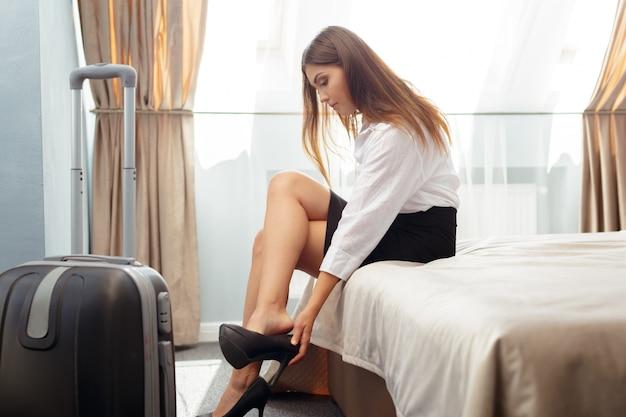 Geschäftsfrau, die auf bett im hotelzimmer sitzt