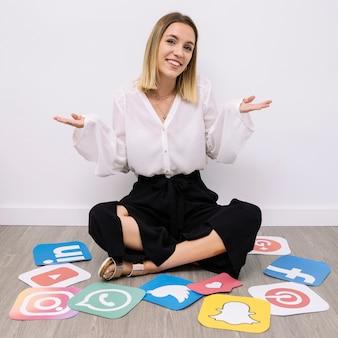 Geschäftsfrau, die auf boden mit den social media-ikonen zucken sitzt
