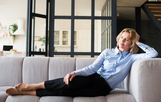 Geschäftsfrau, die auf couch stillsteht