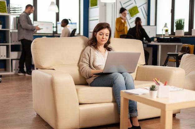 Geschäftsfrau, die auf dem laptop auf der couch im start-up-büro sitzt, während ein vielfältiges team im hintergrund arbeitet und statistikdaten analysiert