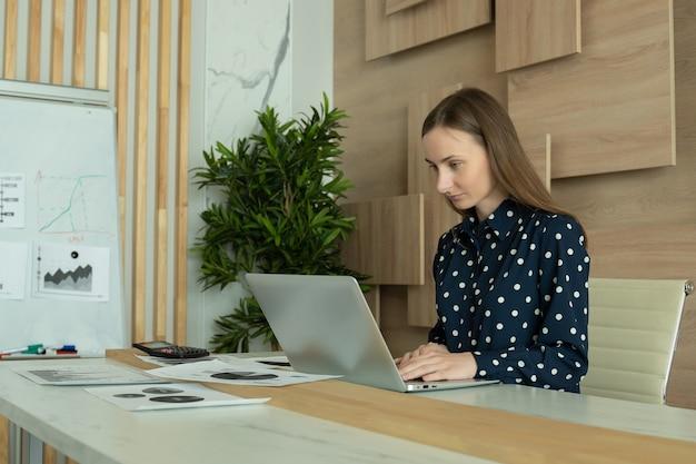 Geschäftsfrau, die auf dem laptop schreibt, der online am schreibtisch arbeitet
