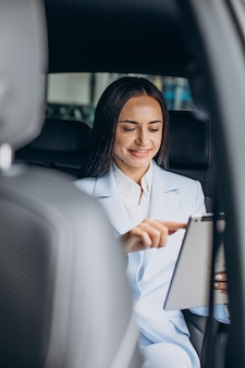 Geschäftsfrau, die auf dem rücksitz ihres autos an tablet arbeitet