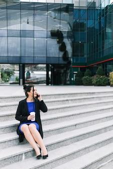 Geschäftsfrau, die auf dem treppenhaus spricht auf mobiltelefon sitzt