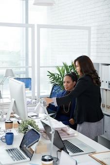 Geschäftsfrau, die auf den computerbildschirm zeigt und kollegen nach ungenauigkeiten in berichten oder präsentationen fragt.