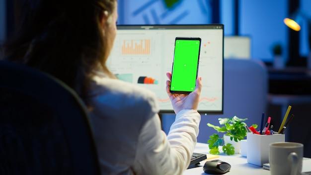 Geschäftsfrau, die auf den grünen bildschirmmonitor des smartphones schaut, das spät nachts am schreibtisch im geschäftsbüro sitzt. freiberufler, der die desktop-monitoranzeige mit grünem mockup beobachtet, chroma-key macht überstunden