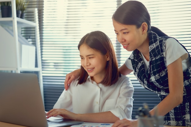 Geschäftsfrau, die auf den laptop schaut, der die arbeitshinweise von teamkollegen, brainstorming-besprechung und neuem startprojekt am arbeitsplatz hört.