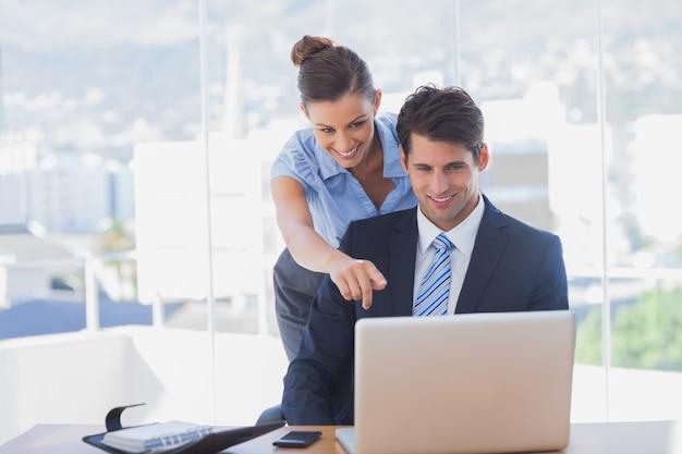 Geschäftsfrau, die auf den laptop zeigt und im büro lächelt