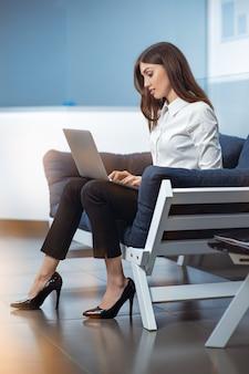 Geschäftsfrau, die auf der couch im büro sitzt, tippt und pc-bildschirm betrachtet.
