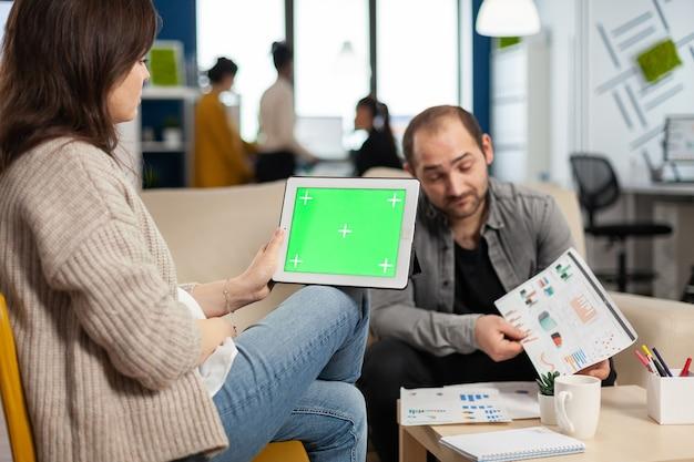 Geschäftsfrau, die auf der couch sitzt und finanzstatistiken analysiert, tablet mit grünem bildschirm hält, während ein vielfältiges team am hintergrund arbeitet