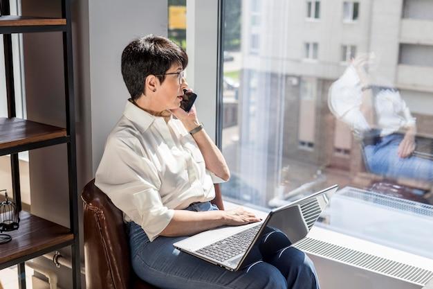 Geschäftsfrau, die auf der telefonseitenansicht spricht
