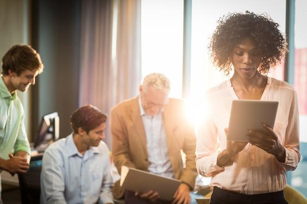Geschäftsfrau, die auf digitalem tablett mit mitarbeiter im hintergrund arbeitet
