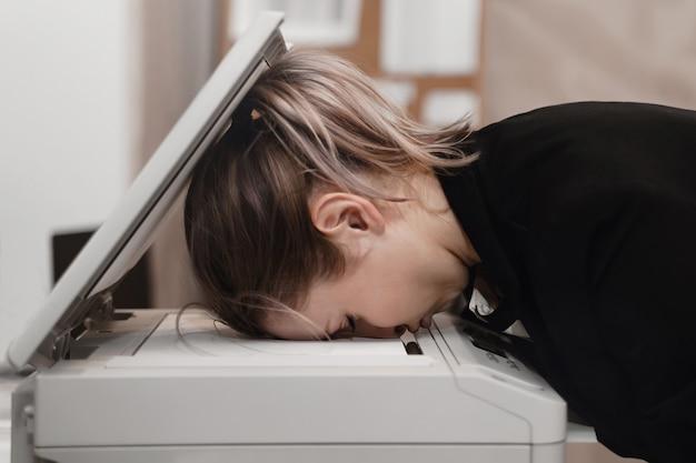 Geschäftsfrau, die auf drucker im büro schläft. überarbeitetes konzept.