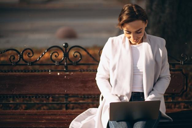 Geschäftsfrau, die auf einer bank arbeitet an computer sitzt