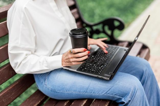 Geschäftsfrau, die auf einer bank im park sitzt
