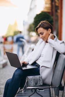 Geschäftsfrau, die auf einer bank sitzt und an einem computer arbeitet