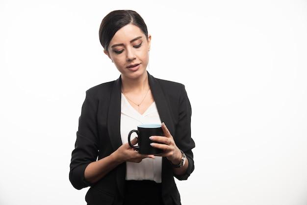 Geschäftsfrau, die auf einer schwarzen tasse auf einem weißen hintergrund schaut. foto in hoher qualität