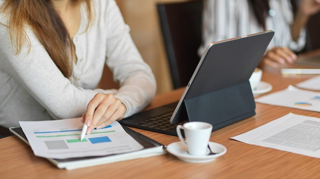 Geschäftsfrau, die auf finanzdiagrammen schaut, während sie einen stylus-stift auf einem holzschreibtisch hält
