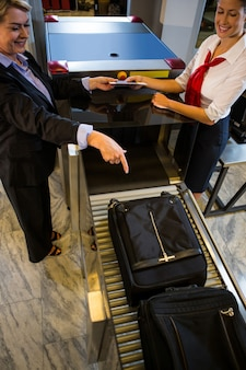 Geschäftsfrau, die auf gepäck zeigt, das auf förderband gehalten wird