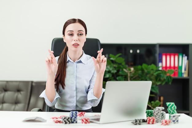 Geschäftsfrau, die auf glück beim spielen des online-kasinos bei der arbeit im büro hofft