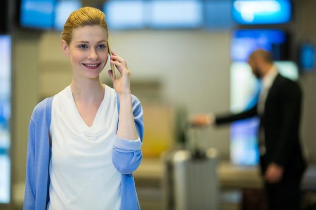 Geschäftsfrau, die auf handy im wartebereich spricht