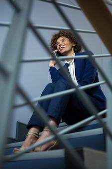 Geschäftsfrau, die auf handy spricht, während auf stufen am konferenzzentrum sitzt
