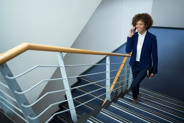 Geschäftsfrau, die auf handy spricht, während schritte am konferenzzentrum klettert