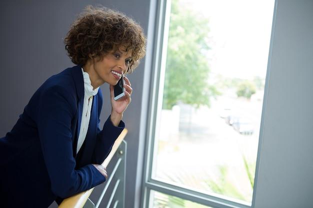 Geschäftsfrau, die auf handy spricht, während sie sich über das treppengeländer im konferenzzentrum beugt