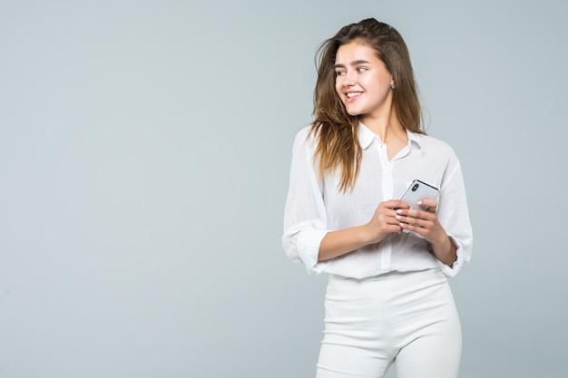 Geschäftsfrau, die auf ihrem handy eine sms sendet - lokalisiert über weißem hintergrund