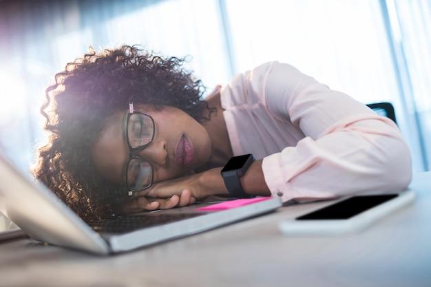 Geschäftsfrau, die auf ihrem schreibtisch schläft