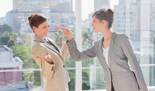 Geschäftsfrau, die auf ihren rivalen zeigt