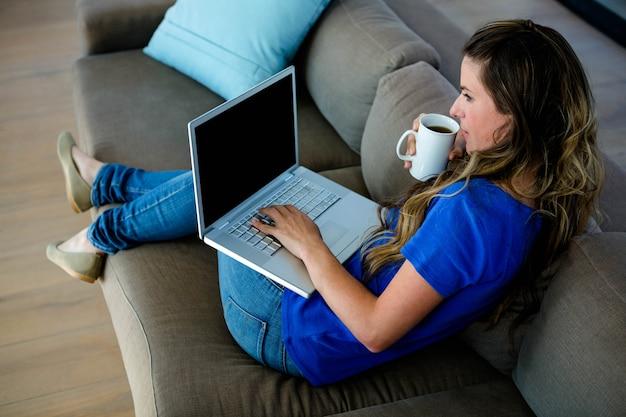 Geschäftsfrau, die auf ihrer couch sitzt, kaffee nippt und auf ihrem laptop schreibt