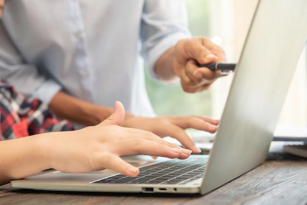 Geschäftsfrau, die auf laptop am arbeitsplatz frau schreibt, die in bürohandtastatur arbeitet.