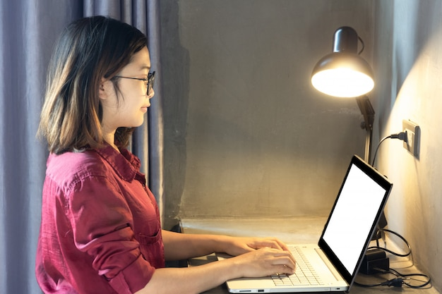 Geschäftsfrau, die auf laptop mit leerem weißem schirm für spott herauf schablonenhintergrund mit lampe schreibt