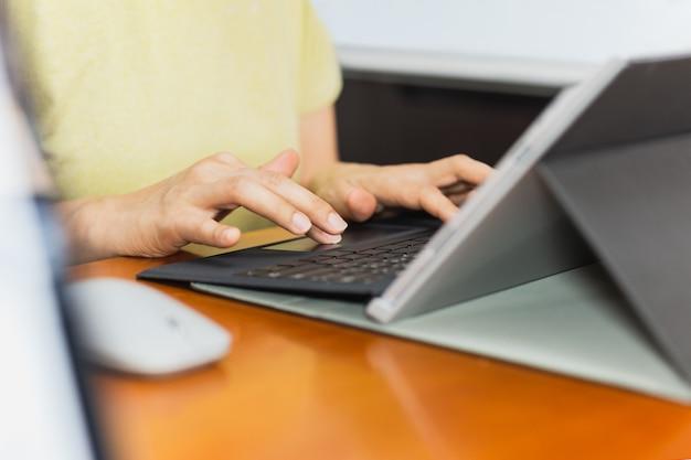 Geschäftsfrau, die auf laptop-tastatur schreibt, die von zu hause aus konzeptionell arbeitet.