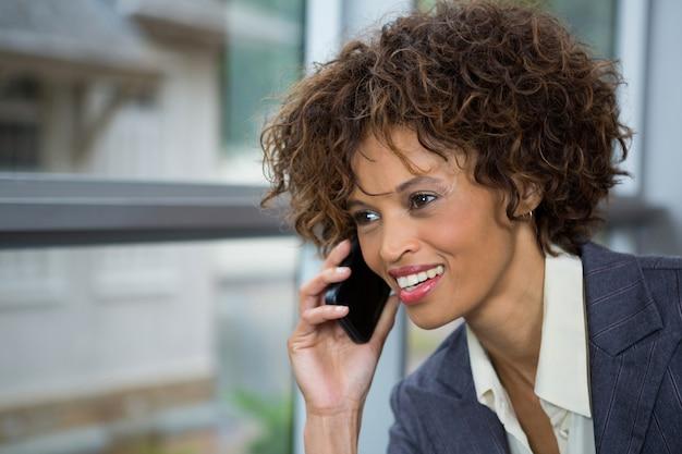 Geschäftsfrau, die auf mobiltelefon am konferenzzentrum spricht