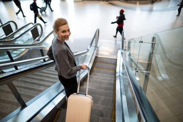 Geschäftsfrau, die auf rolltreppe mit gepäck steht