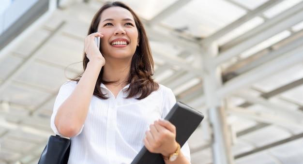 Geschäftsfrau, die auf smartphone spricht und sich auf draußen beim gehen heraus von den gebäuden freut