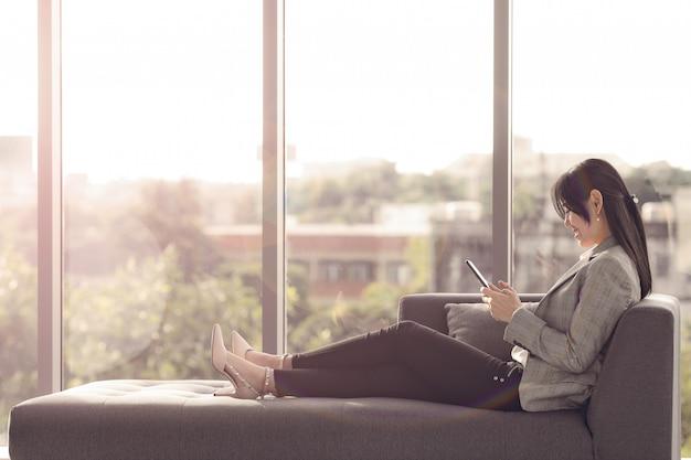 Geschäftsfrau, die auf sofa sich entspannt.