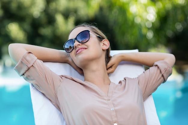 Geschäftsfrau, die auf sonnenliege entspannt