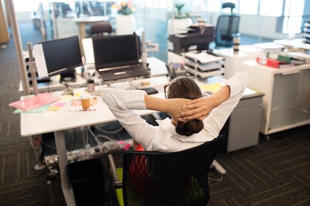 Geschäftsfrau, die auf stuhl durch schreibtisch im büro entspannt